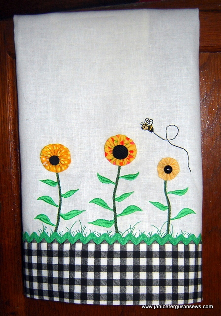 Yo-yo flowers with button centers, rick rack and a turn tube hem transform a plain white dishtowel to something more interesting.